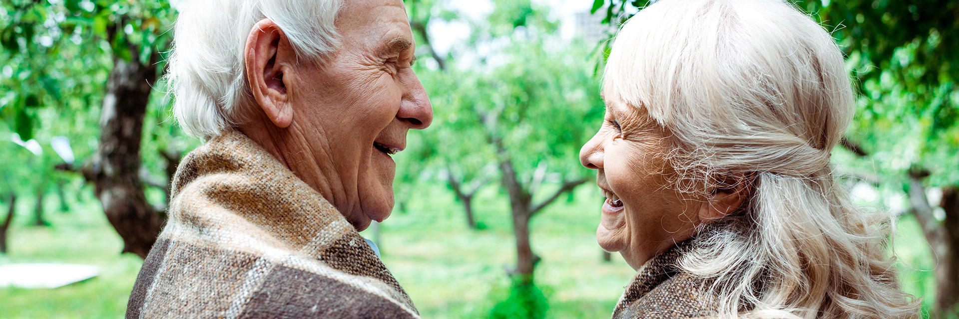 head shot of senior couple smiling at each other outside